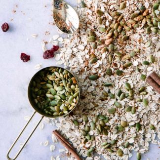 oats, pumpkin seeds, cranberries, and cinnamon on white marble background
