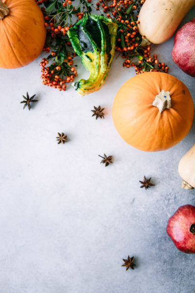 pumpkins, squash, pomegranates, and anise on a blue table