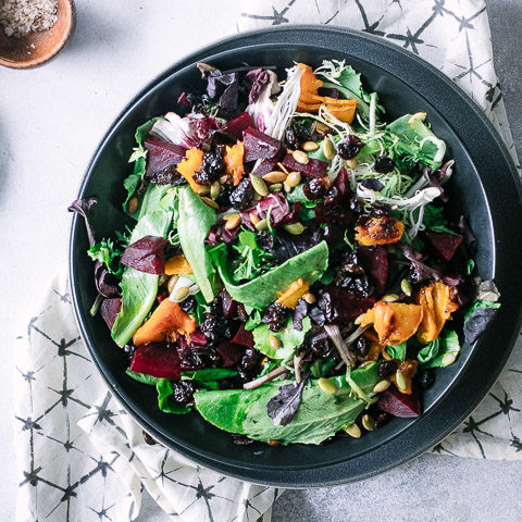 a fall vegetable salad in a black bowl on a white table