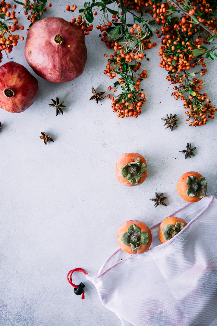 A reusable produce bag with persimmons on a white table