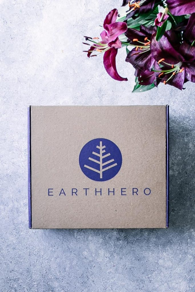 A cardboard Earth Hero subscription box on a blue table with flowers