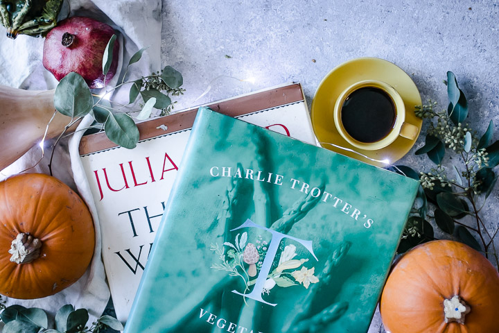 julia child and charlie trotter seasonal cookbooks on a blue table