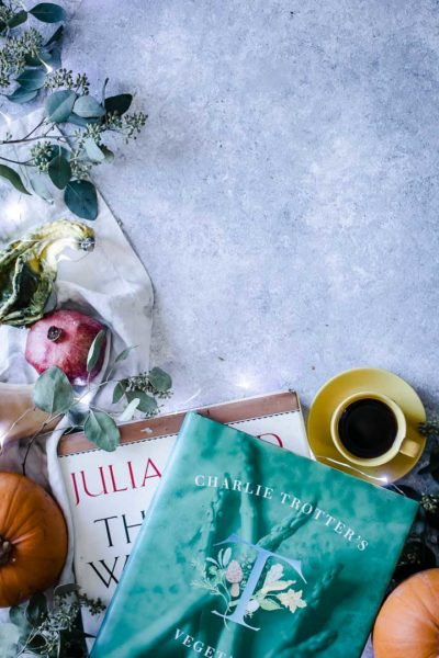 cookbooks and coffee on a blue table with winter vegetables and fruit