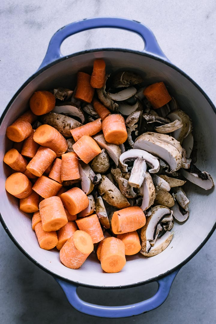 a blue dutch oven with cut mushrooms and carrots