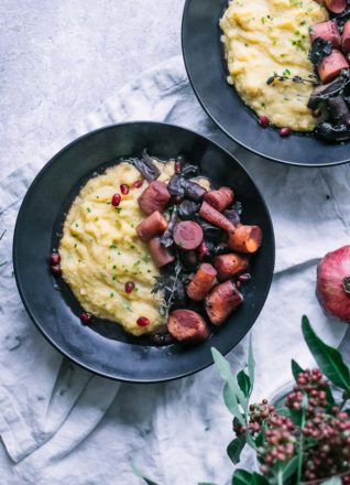 a black bowl with polenta and braised mushrooms and carrots