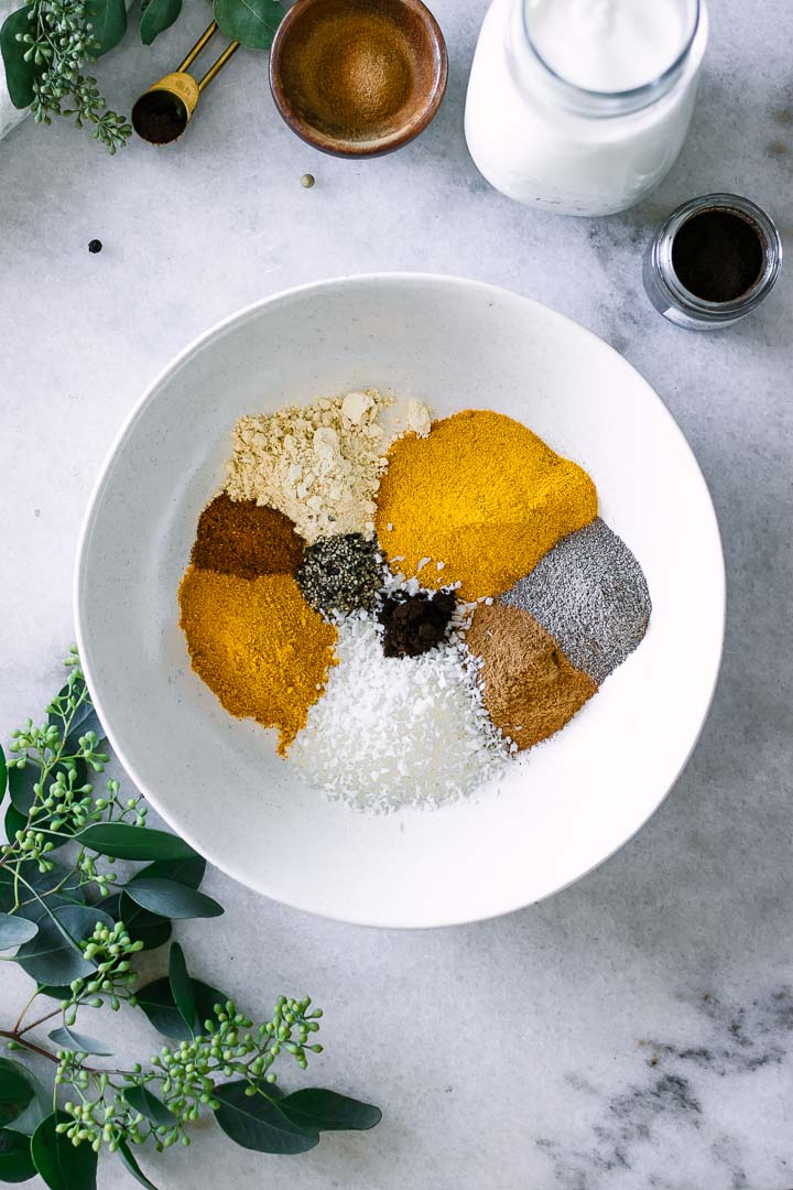 Turmeric, ginger, coconut, cinnamon, black pepper, nutmeg, and cardamom in a white bowl.