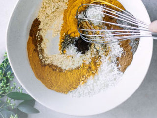 "a white bowl with spices being mixed by a hand with a whisk and the words ""homemade golden milk spice mix"" in black and orange letters"