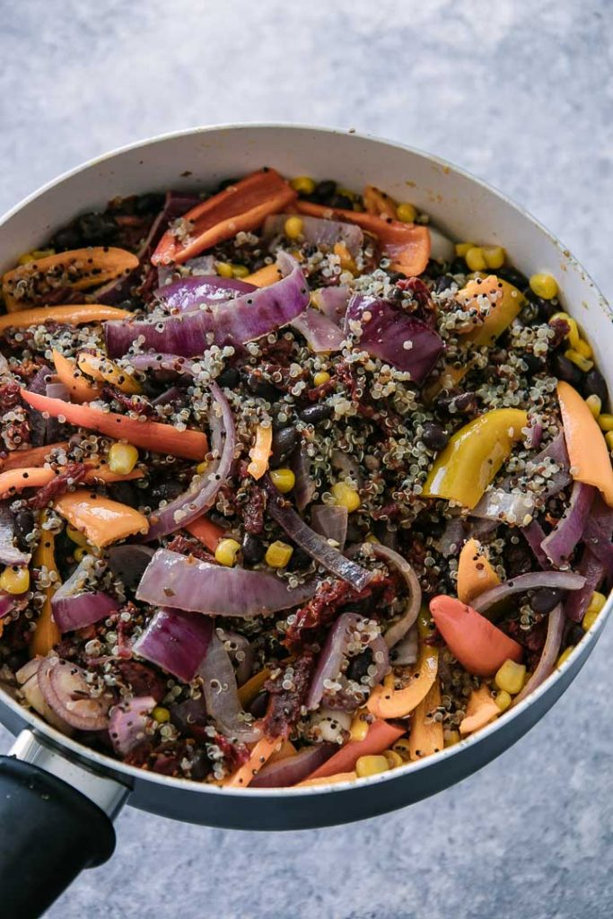 a black bean and quinoa salad in a black pan with colorful vegetables