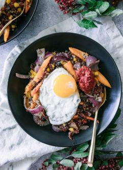 black beans, quinoa, bell peppers, onion, corn, and spicy harissa with an egg on top in a black bowl