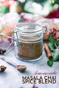 """a small jar of masala chai spice blend with a small wooden spoon and the worlds """"homemade masala chai spice blend"""" in black writing"""