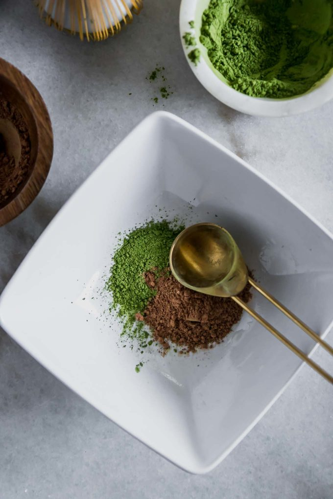 a bowl with matcha powder and cocoa powder and a gold spoon
