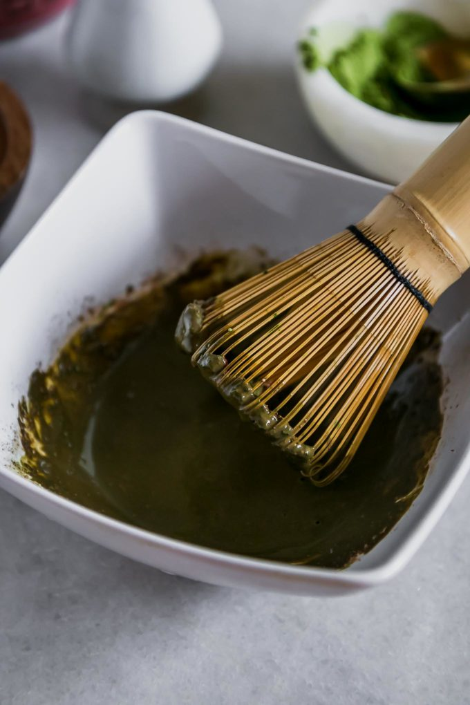 a wooden matcha whisk in a white bowl with dissolved matcha and mocha powders in water