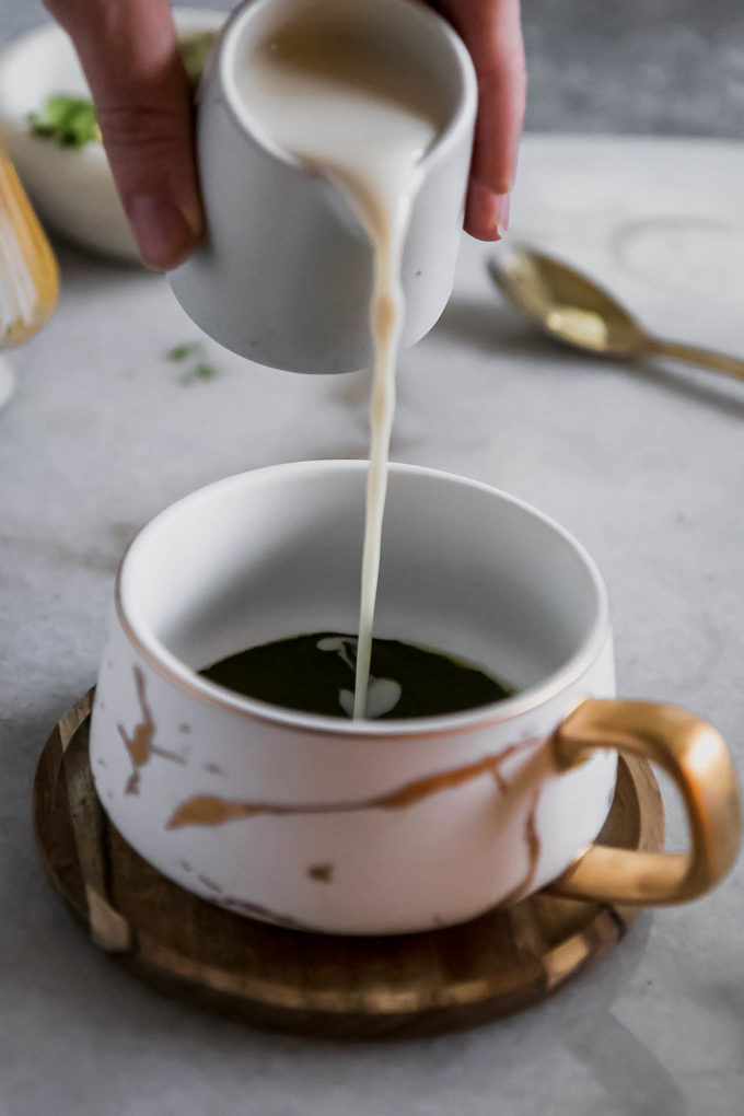 a hand pouring milk into a white mug filled with matcha tea