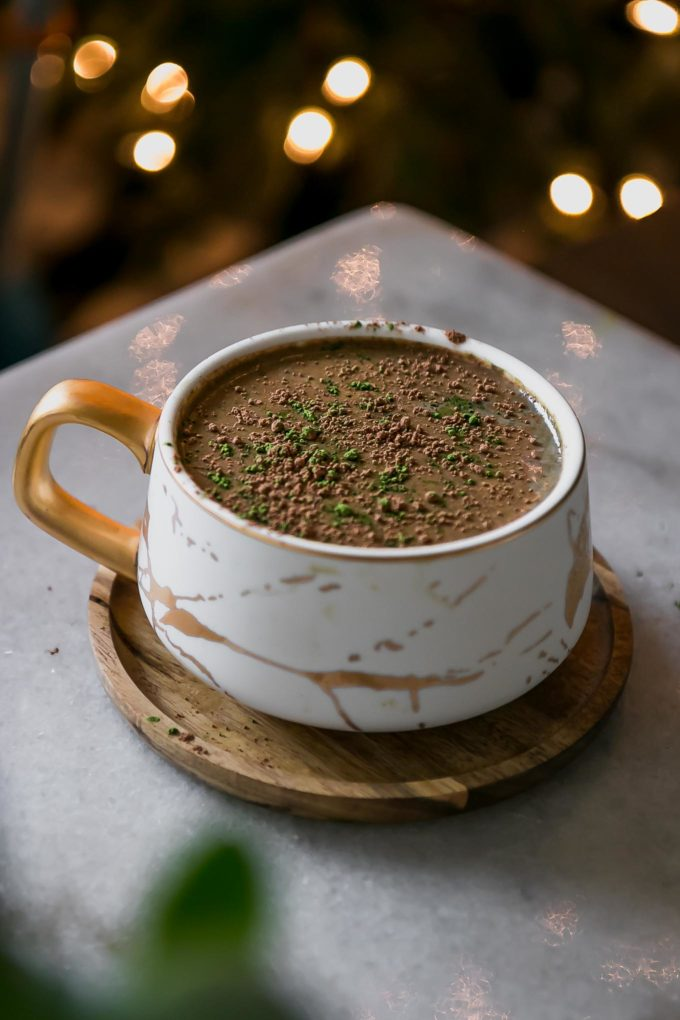 a mocha matcha latte in a white mug on a table with holiday lights in the background