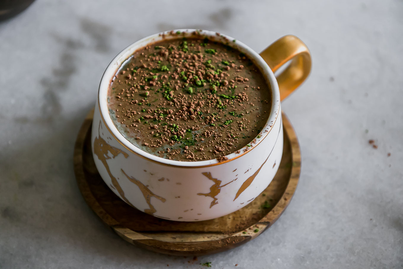 a mocha latte with green matcha powder in a white mug on a white table