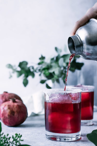 a hand pouring a pomegranate margarita into a glass with a salt and sugar rim