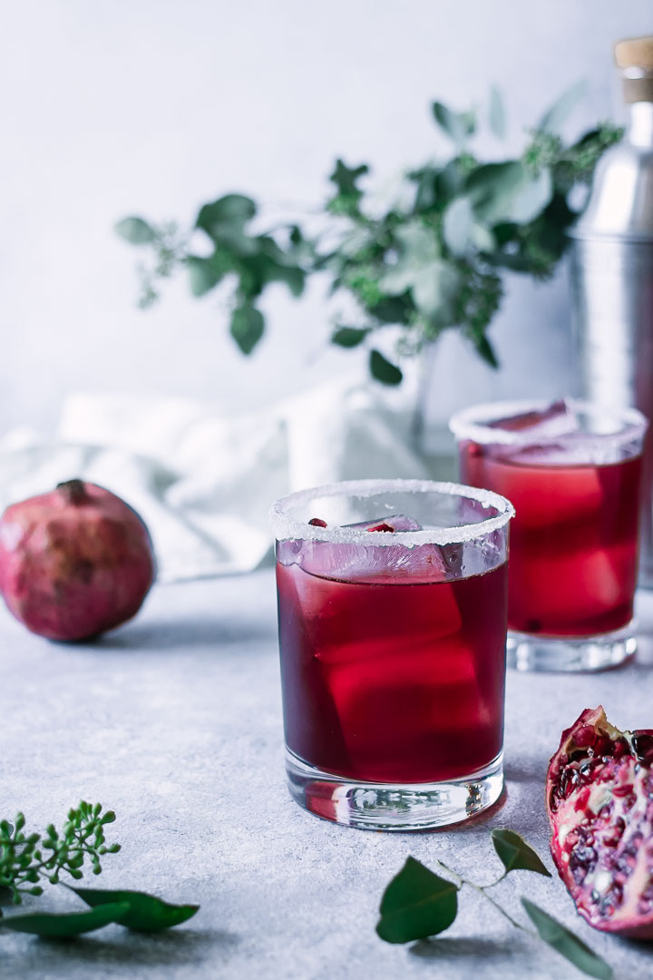 two red margaritas on a blue table with a pomegranate and green leaves