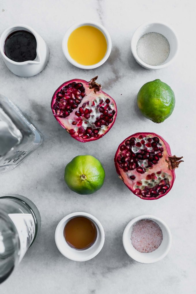 pomegranates, limes, tequila, triple sec, agave nectar, salt, and sugar on a marble table