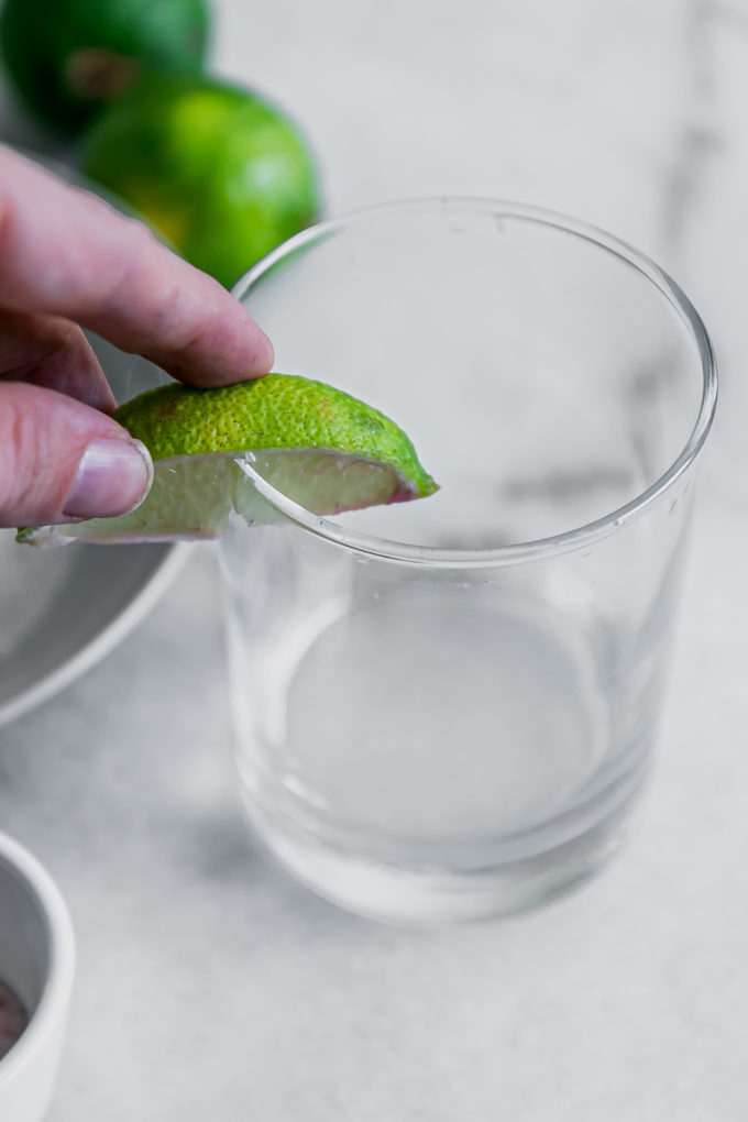 a hand rubbing a cut lime around the rim of a cocktail glass