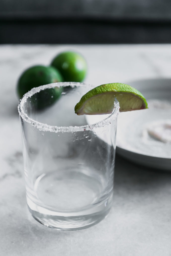 a cocktail glass with a sugar and salt rim and a slice of lime on a white table with limes in the background