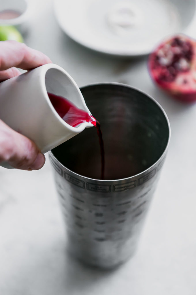 a hand pouring pomegranate juice into a cocktail shaker