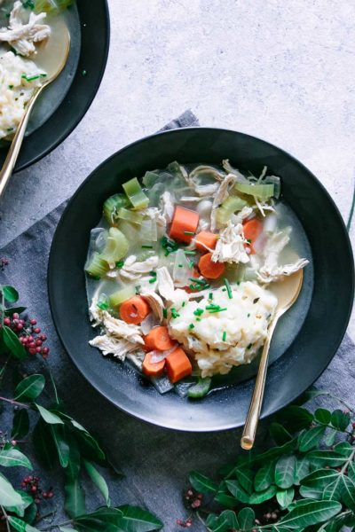 two bowls of chicken and dumplings with cheddar and chives