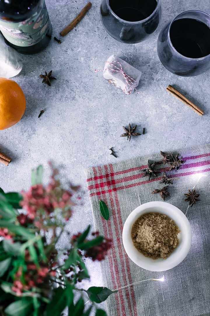 brown sugar, cinnamon, star anise, cloves, oranges, and winter flowers on a blue table
