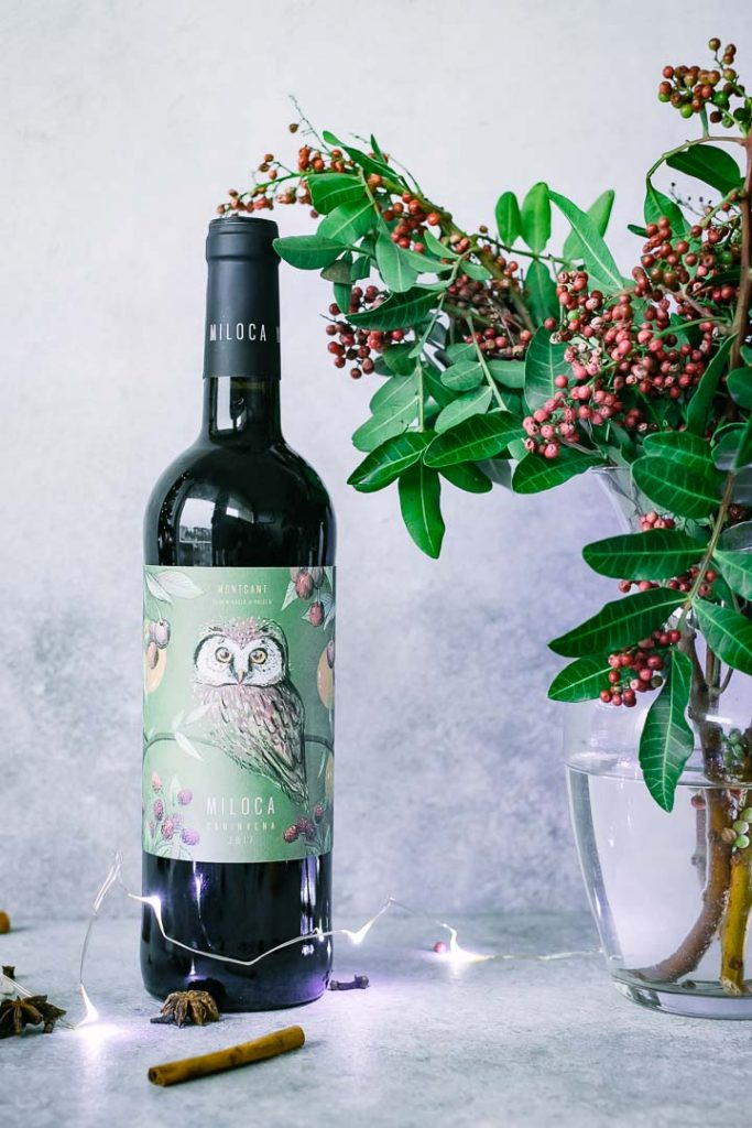 a bottle of red wine on a table with christmas flowers