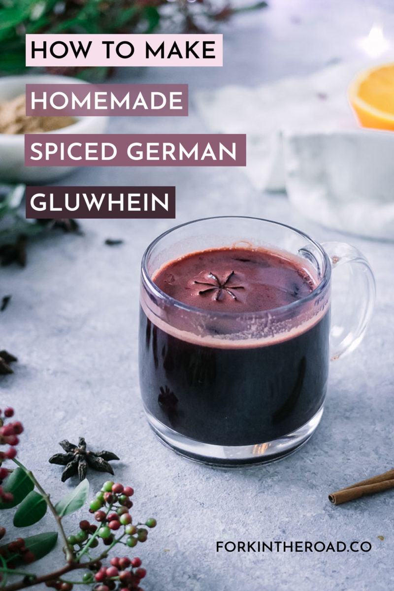 a glass mug with german gluwhein, a spiced mulled red wine, on a blue table with spices and holiday plants