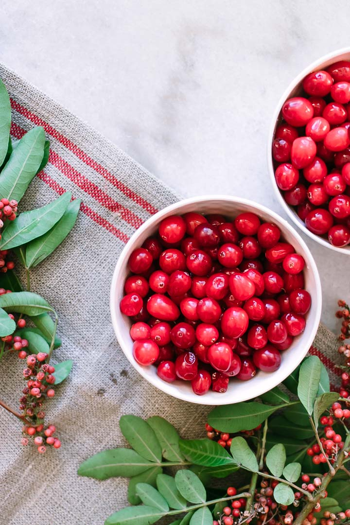 two bowls of cranberries on a white table with green leaves