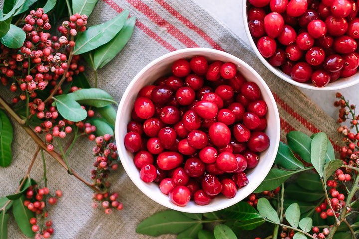two small bowls of cranberries on a white table with leaves