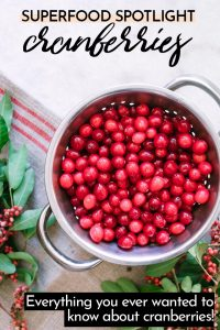 """Cranberries in a colander with the words """"superfood spotlight on cranberries"""" in black writing"""