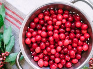"Cranberries in a colander with the words ""superfood spotlight on cranberries"" in black writing"