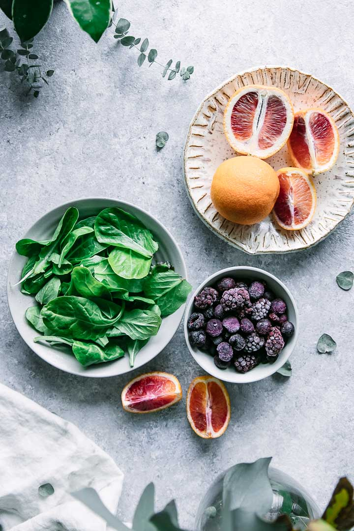 a bowl of spinach, a bowl of frozen berries, and a plate with blood oranges on a blue table