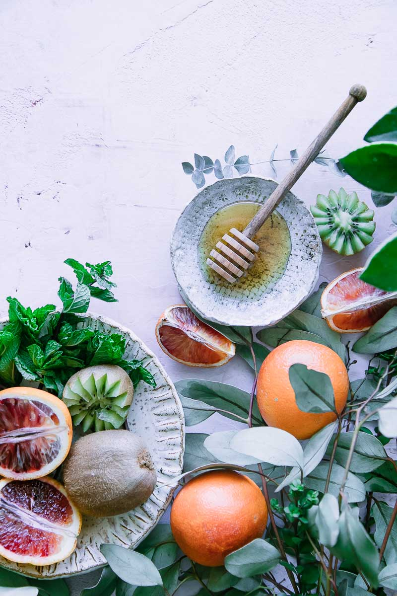 blood oranges, kiwi, and small plate of honey with a honey drizzler on a pink table with green leaves
