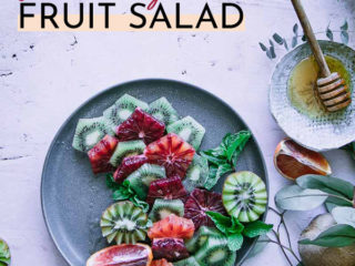 """a fruit salad with oranges and kiwis on a blue plate and the words """"blood orange kiwi fruit salad"""" in black and orange writing"""