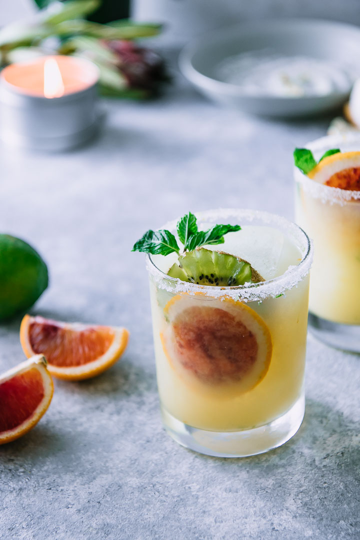 two highball glasses with margaritas, blood oranges, and kiwi and a salted rim