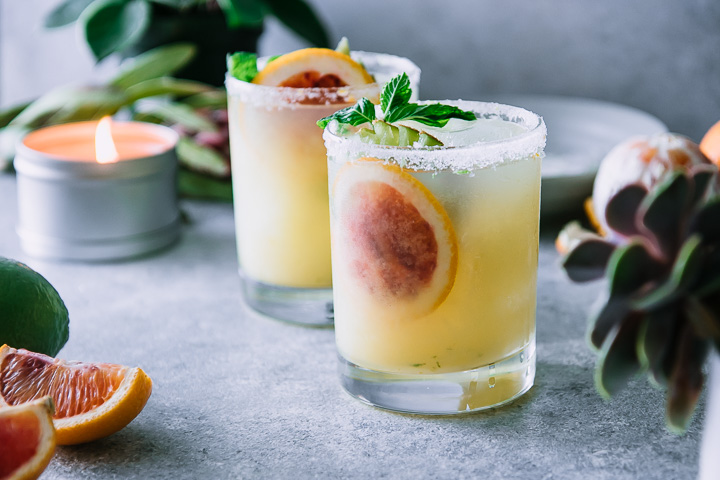 two margaritas on a blue table with sliced blood oranges and a candle with a green plant in the background