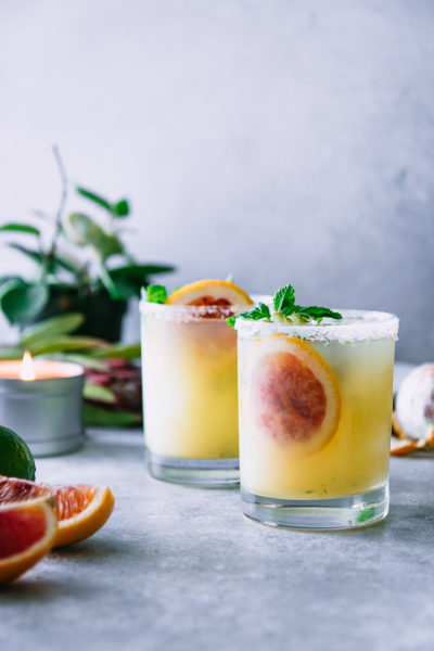 two salted margaritas on a white table with plants and candles