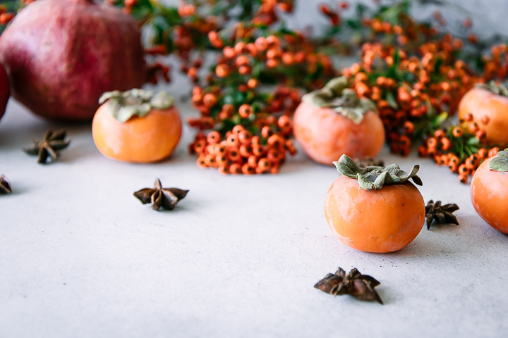 pomegranates and persimmons on a white table with star anise