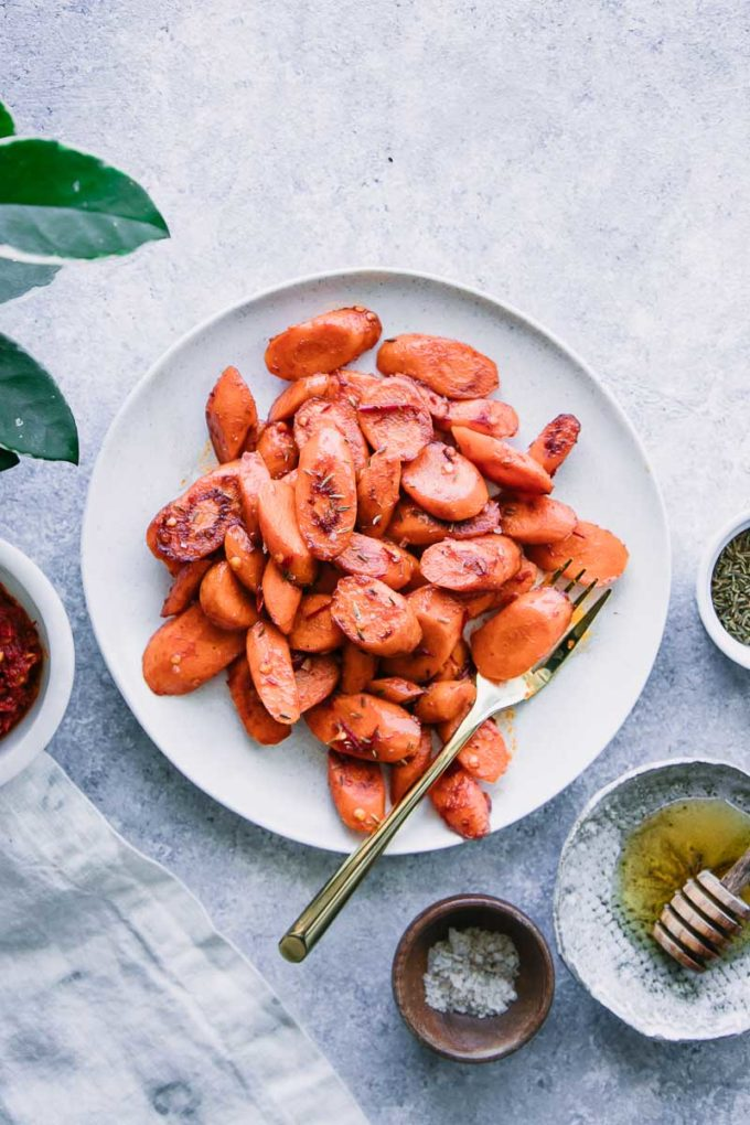 cooked carrots on a white plate with a gold fork and a side of honey and harissa sauce on a blue table
