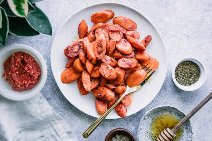 a plate of roasted carrots on a blue table with a side of sea salt and a white napkin