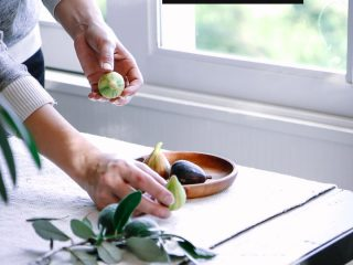 a woman plating figs on a wooden tale in front of a window