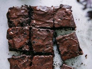 9 sliced brownies on a white marble table with an espresso maker with fresh espresso grounds