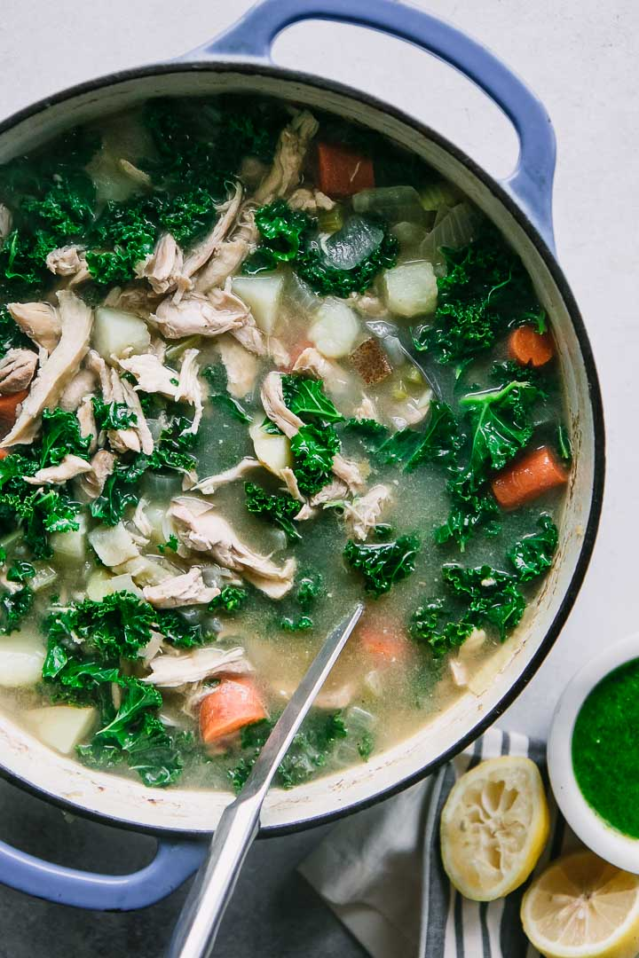 a large blue ceramic dutch oven filled with chicken kale and potato soup with a silver ladle