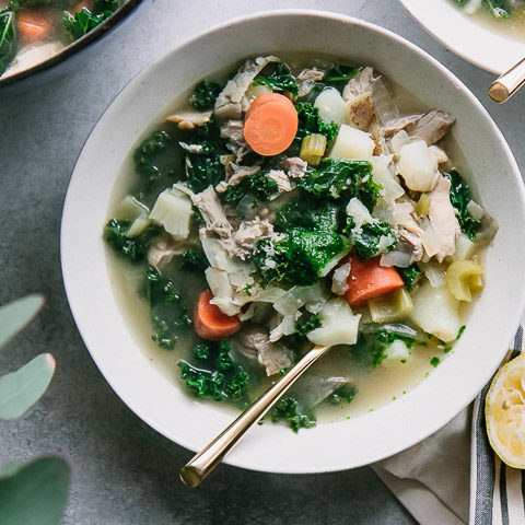 a bowl of chicken soup with potatoes, kale, and carrots on a blue table with a half a lemon