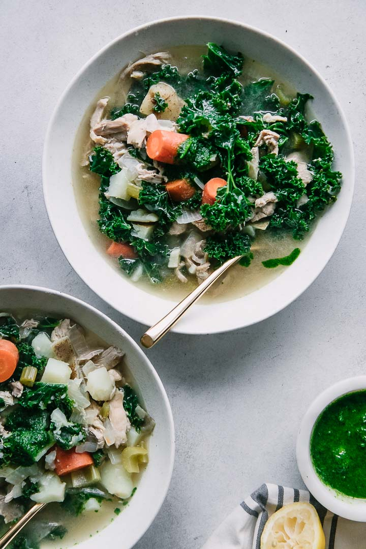 two bowls of chicken kale soup on a white table