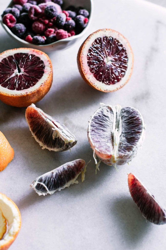 peeled blood oranges on a marble countertop