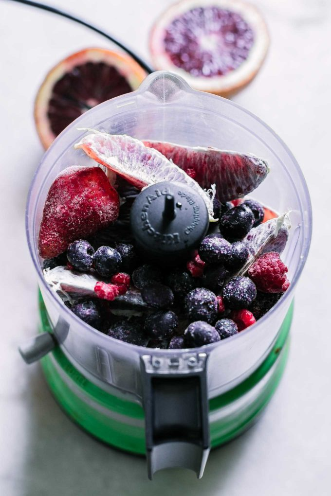 blood oranges and frozen berries inside a small food processor