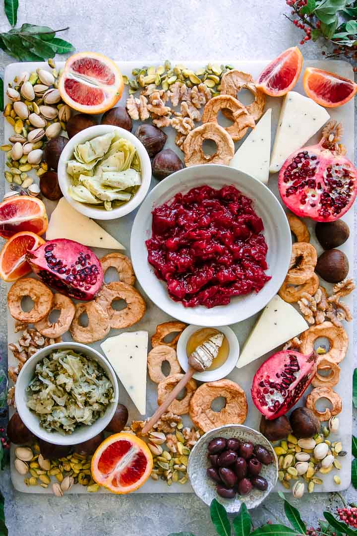 a platter with oranges, pomegranates, chestnuts, walnuts, pistachios, and olives on a white table with green leaves